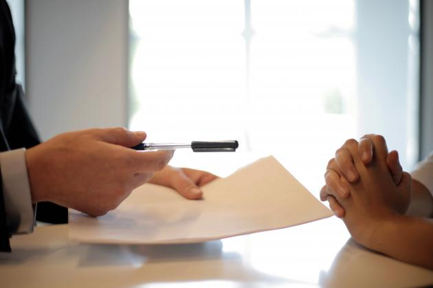 Business person giving employee a document to sign | Credit: Andrea Piacquadio from Pexels